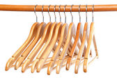 Wooden clothes hangers on the bar. — Stock Photo