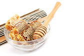 Honey comb in a glass bowl and wooden stick. — Photo