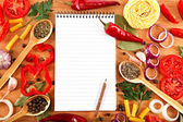 Vegetables, spices and recipes notepad on wooden cutting board. — Stock Photo