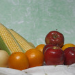 Stock Photo: Organic fruits on green background (Still life)