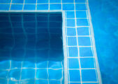 Blue tiles in swimming pool water — Foto Stock