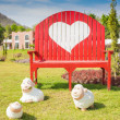 Green grass and heart shape on bench in the garden — Stock Photo