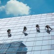 Group of workers cleaning windows service on high rise building - Stockfoto
