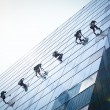 Foto Stock: Group of workers cleaning windows service on high rise building