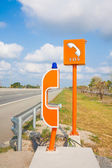 SOS sign and phone box on highway, road safety — Stock Photo