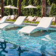 Chaise lounge or chair in swimming pool — Stock Photo