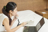 Happy young asian woman working on phone and laptop in bedroom — Stock Photo