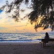 Stock Photo: Woman sit on chairs under tree on beach at sunset