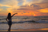 Woman silhouette in the sunset and pointing — Stock Photo