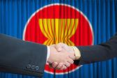 ASEAN Economic Community in businessman handshake — Stock Photo