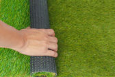 Artificial turf green grass roll with hand — Stock Photo
