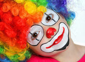 Pretty girl with face painting of a clown — Stock Photo