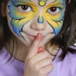 Pretty girl hushing with finger. Face painting of butterfly. — Stock Photo #18239701