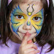 Pretty girl hushing with finger. Face painting of a butterfly. — Stock Photo