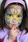 Hezká dívka okřikují prstem. malování na obličej motýla. — Stock fotografie