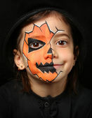 Pretty girl with face painting of a pumpkin — Stock Photo