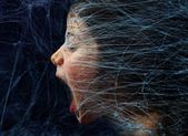 Scared girl trapped in a spider web — Stock Photo