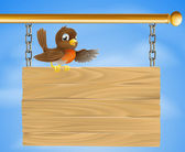 Robin sitting on old sign — Stock Vector
