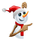 Happy snowman in Santa hat pointing — Stock Vector
