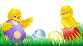 Cute yellow chicks and Easter eggs — Stock Vector