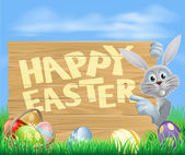 White Easter bunny pointing at sign — Stock Vector
