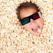 Stock Photo: Young girl buried in popcorn
