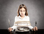 Little girl roped sitting at table — Stock Photo