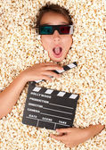 Young girl buried in popcorn — Stock Photo