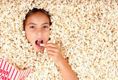 Little girl buried in popcorn — Stock Photo