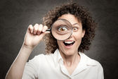 Woman looking through magnifying glass — Stock Photo