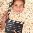 Stock Photo: Little girl buried in popcorn