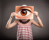 Little girl holding an eye — Stock Photo