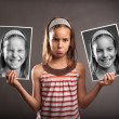 Sad little girl holding two photos of herself — Stock Photo #28449913