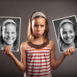 Sad little girl holding two photos of herself — Stock Photo