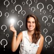 Stock Photo: Young womholding lightbulb with interrogation symbols