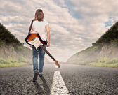 Young musician woman walking on a road — Stock Photo