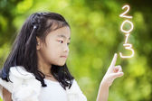Little girl write the numbers 2013 — Stock Photo