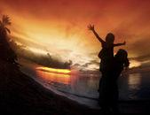 Mor och hennes barn siluetter på stranden — Stockfoto