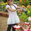 Unidentify girl take a flower photo - Stock Photo