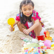 Stock Photo: Girl is playing with her toys on the beach