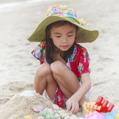 Girl is playing with her toys on the beach — Stock Photo