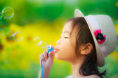 Asian little girl is blowing a soap bubbles in sunflower garden — Stock Photo