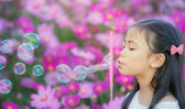 Asian little girl is blowing a soap bubbles — Stock Photo
