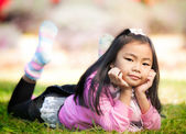Little asian girl resting on green grass — Foto de Stock