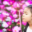 Asian little girl is blowing a soap bubbles — Stock Photo #40384533