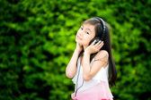 Cute kid listening to music on headphones  — Stock Photo