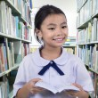 Cute schoolgirl smiling while reading — Stock Photo #50360243