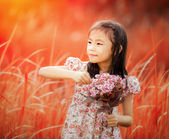 Asian little girl laughing in a meadow — Stock Photo