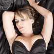 Lingerie and black sheets — Stock Photo