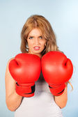 Beautiful woman with attitude wearing red boxing gloves — Stock Photo